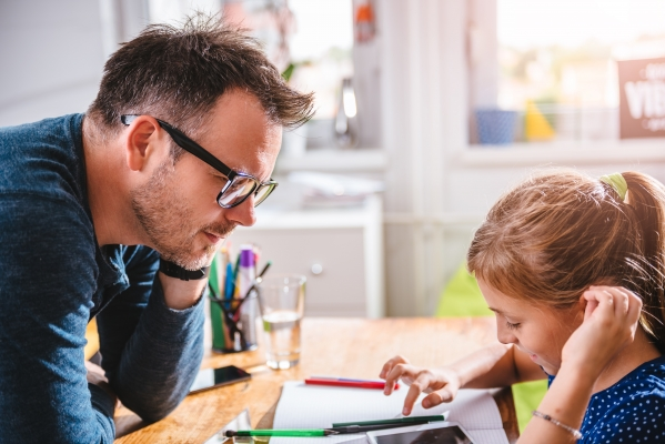 A man watches a child using an electronic device